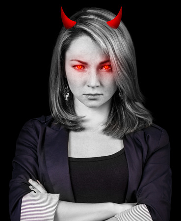 wicked woman: Crazy, angry business woman with red eyes and devil horns over black background Stock Photo