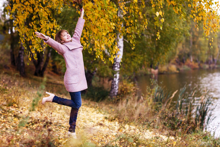 rejoices: Happy young woman in forest rejoices in autumn Stock Photo