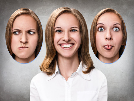 Young girl changes her face portraits with different emotions over gray background Stock Photo