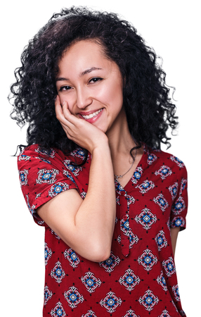 Young woman smiling with curly black hair isolated on white background