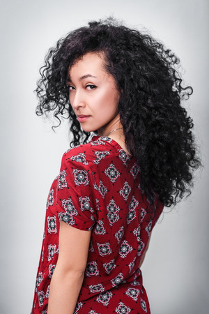 Young beautiful woman with curly black hair over gray background