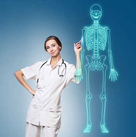 stetoscope: Doctor woman pointing on drawing human skeleton.