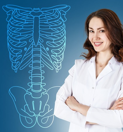 physiotherapist: Doctor woman standing near drawing human skeleton