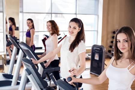 Young women running on treadmill in gym.