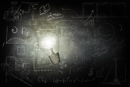 Bright bulb Illuminates icons on chalkboard Imagens