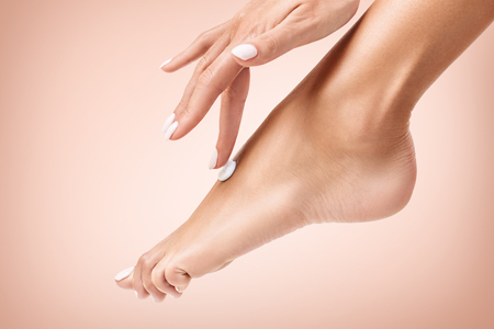 Woman applying cream on her beautiful feet.
