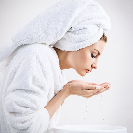 Young woman washing face with clean water.