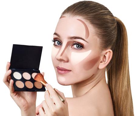 Mujer joven que sostiene la paleta para contornear la cara.