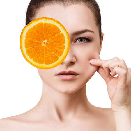 Woman covering eye by orange slice.