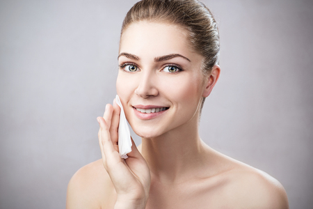 Young woman cleaning her face by napkins.