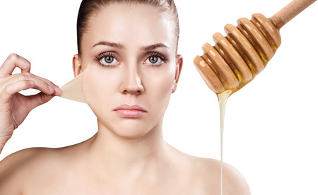 elasticidad: Young woman prepare for honey facial mask.