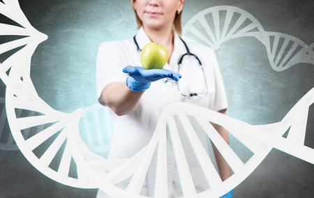 Woman doctor standing among large dna chain. Stock Photo