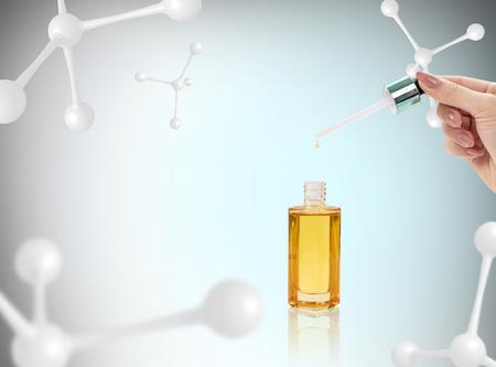 Anti-aging cosmetics oil for skin among molecules. Foto de archivo