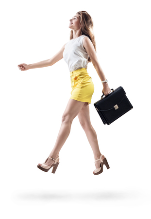 Young cheerful woman walking with briefcase. Stock Photo