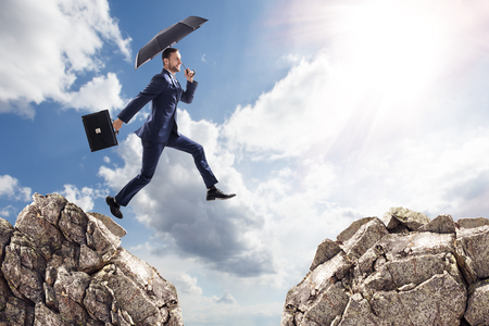 Businessman with umbrella jumping on mountains. Stock Photo