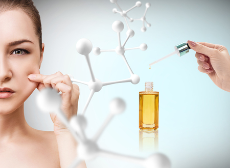elasticidad: Aceite cosmético que aplica en la cara de la mujer joven.