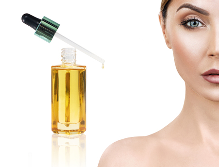 Cosmetische olie aanbrengen op het gezicht van een jonge vrouw. Stockfoto - 85890957