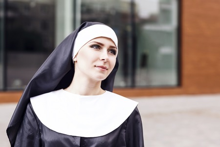 Young nun with bright makeup looking up outdoors.