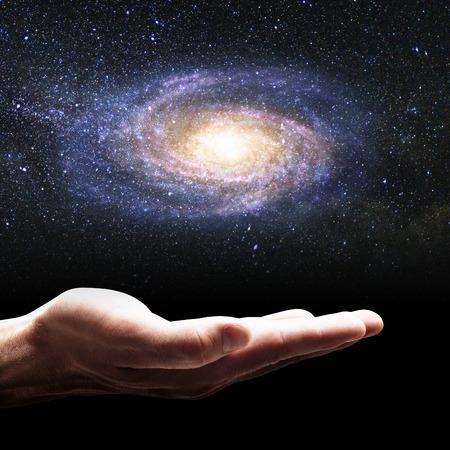 Geschäftsmannhand, die kleine Galaxie hält.