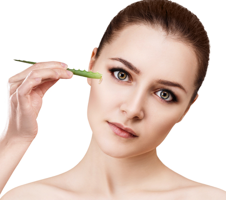 aging face: Young woman uses aloe vera oil for skin. Stock Photo