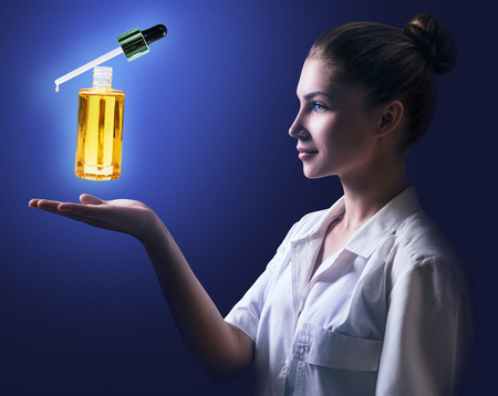 Young cosmetologist woman presents cosmetics oil Stock Photo