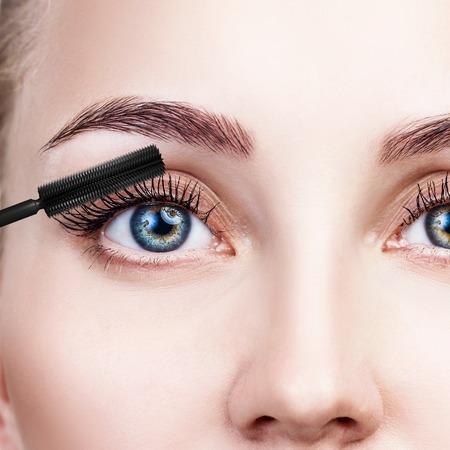 Woman applying mascara on eyelashes with brush. Stock Photo