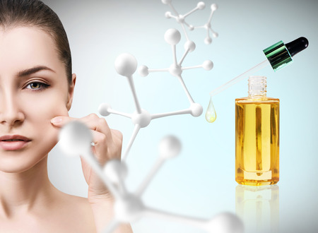 elasticidad: Cosmetic oil applying on face of young woman.