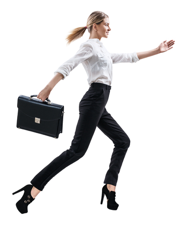 Happy young woman in formal wear jumping .