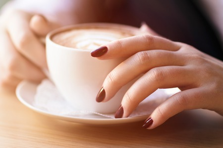 Woman holding cup of capuccino on wooden table. Stock Photo