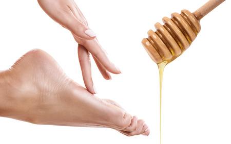 Honey flows down from spoon near female foot.