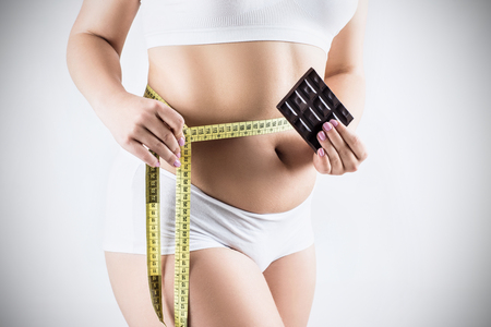 Fatty woman with measuring tape holds chocolate bar. Stock Photo