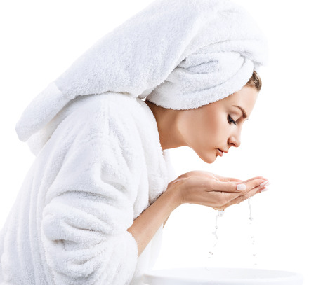 Young woman washing face with clean water. Isolated on white background