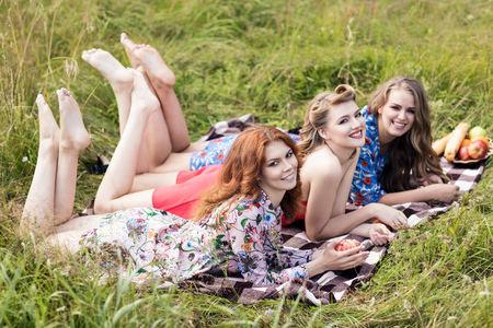 Young beautiful women lying on plaid in summer park. Stock Photo