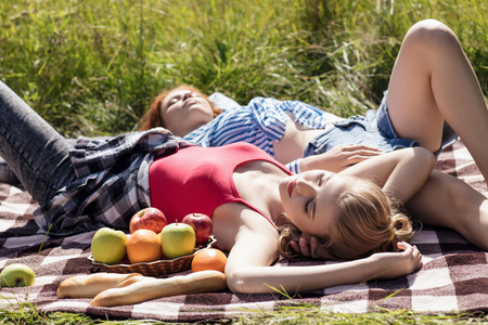 Young beautiful women have picnic in summer park. Stock Photo