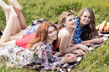 Young beautiful women on picnic in summer park.