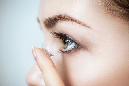 Zbliżenie młodej kobiety noszącej soczewki kontaktowe. Zdjęcie Seryjne