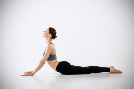 Attractive young woman practicing yoga over gray background.