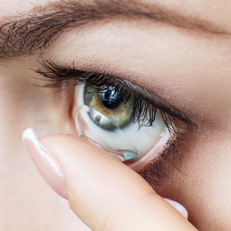 Close-up shot of young woman wearing contact lens for a better view. Over blue background.