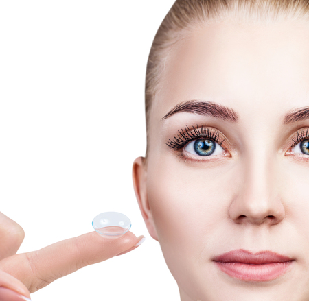 Contact lens on index finger near beautiful female face