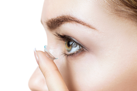 Close-up shot of young woman wearing contact lens. Stock Photo