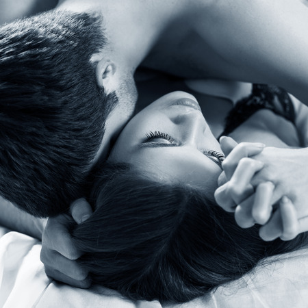 Young passionate couple making love in bed.