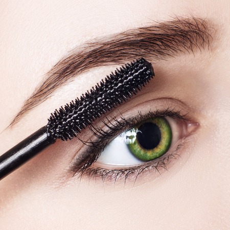 Woman applying mascara on eyelashes with brush. Stock Photo