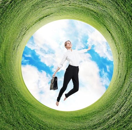 Business woman jumps in rotated field with green grass.