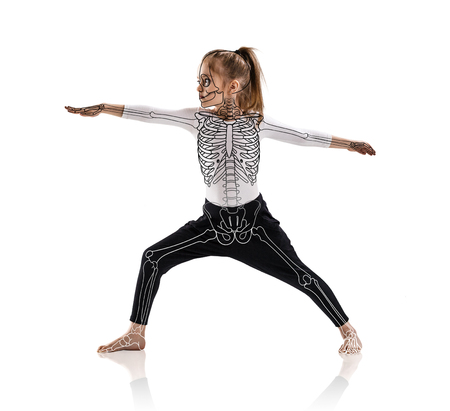 Little girl in a yoga pose with drawing skeleton.