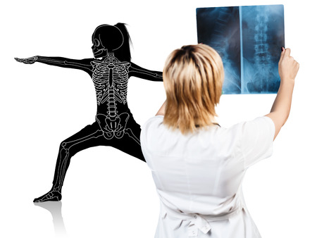 Female doctor looks on x-ray of little girl silhouette. Stock Photo