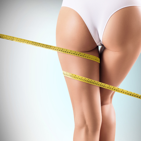 Female buttocks with measuring tape shows slimming result.