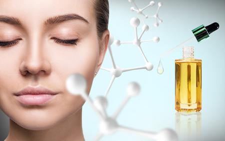 Cosmetic primer oil near woman face with big molecule chain. Stockfoto