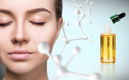 Cosmetic primer oil near woman face with big molecule chain. Stok Fotoğraf - 100186685
