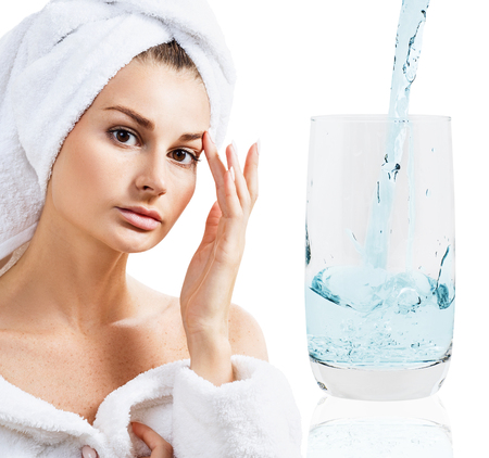 Young sensual with towel on head near glass with clear water.