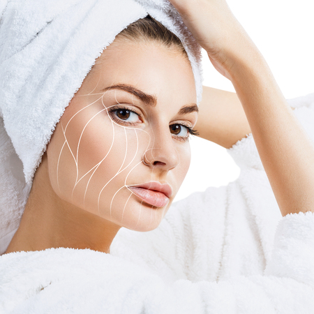 Donna in accappatoio con linee di sollevamento sul viso.
